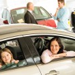 Mother and daughter trying car in dealership — Stock Photo #29786835