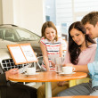 Stock Photo: Couple reading papers in car dealership