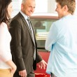 Portrait of car dealer with customers — Stockfoto