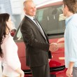 Couple buying a car in dealership — Stock Photo