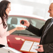 Salesman handing car keys to woman — Stock Photo
