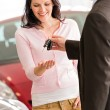 Stock Photo: Womreceiving keys of new car