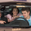 Young couple testing car in showroom — Stock Photo #29786901