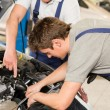 Middle aged car repairman helping colleague — Stock Photo