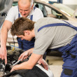 Caucasian car mechanics working together — Stock Photo
