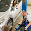Stock Photo: Car repairmen changing tire in garage