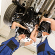 Foto Stock: Auto mechanics working underneath car