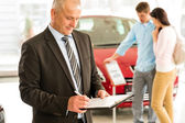 Caucasian salesman in car showroom — Stock Photo