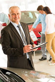 Portrait of salesman working in car dealership — Stock Photo