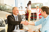 Customer and car salesman shaking hands — Stock Photo
