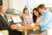 Couple reading papers in car dealership — Stock Photo