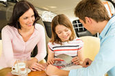 Family looking at color swatches car showroom — Stock Photo