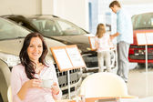 Customer drinking coffee in car dealership — Stock Photo