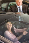 Caucasian woman testing car in showroom — Stockfoto