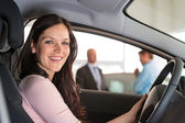 Lachende vrouw die zit in auto in showroom — Stockfoto