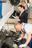 Middle aged mechanic examining engine — Stock Photo