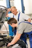 Elderly mechanic supervising colleague's work — Stock Photo