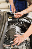 Car mechanic passing a wrench to colleague — Stock Photo