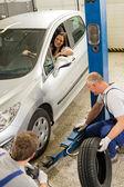 Car repairmen changing tire in garage — Stock Photo