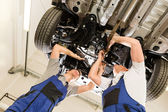 Auto mechanics working underneath a car — Stockfoto