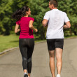 Rear view of couple friends jogging together — Foto Stock