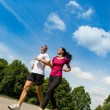 Stock Photo: Low angle view of couple running outdoors