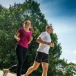 Stock Photo: Young couple jogging in a park