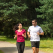 Young smiling couple running in park — Stock Photo