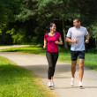 Cheerful couple friends running in park — Stock Photo