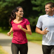 Cheerful Caucasian couple running outdoors — Stock Photo #31302381