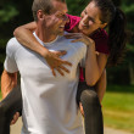 Smiling man giving piggyback ride his girlfriend — Stock Photo