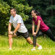 Female and male runner stretching outdoors — Stock Photo #31302433