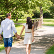 Rear view of walking couple in park — Stock Photo
