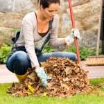 Young woman raking dry leaves autumn backyard — Stock Photo
