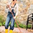 Smiling woman raking leaves fall housework garden — Stock Photo #31303109