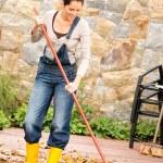 Smiling woman raking leaves fall housework garden — Stock Photo