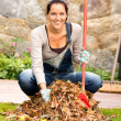 Cheerful woman sweeping leaves autumn pile backyard — Stock Photo