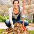 Stock Photo: Cheerful womsweeping leaves autumn pile backyard