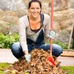 Cheerful woman sweeping leaves autumn pile backyard — Stock Photo