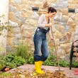 Young woman sweeping autumn leaves veranda — Stock Photo #31303115
