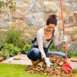 Young woman raking leaves autumn pile veranda — Stock Photo