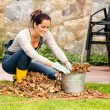 Smiling woman stuffing leaves pail autumn gardening — Stock Photo #31303181
