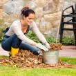Smiling woman stuffing leaves pail autumn gardening — Stock Photo