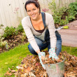 Happy woman filling bucket leaves fall gardening — Stock Photo