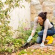 Young woman planting backyard flowerbed autumn — Stock Photo