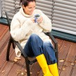 Cheerful woman drinking tea autumn rubber boots — Stock Photo