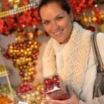 Happy woman buying Christmas balls at shop — Stock Photo