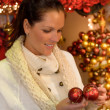 Smiling woman holding Christmas balls at shop — Stock Photo