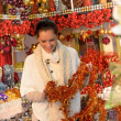 Smiling woman holding Christmas tinsel at shop — Foto Stock