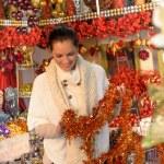 Smiling woman holding Christmas tinsel at shop — Stock Photo